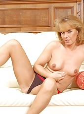 Topless anilos koko relaxes on the sofa and plays with her experienced cougar pussy