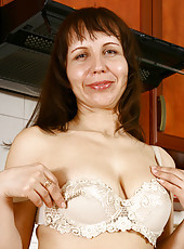Sultry housewife Lana slips off her dress and rubs cream on her big boobs in the kitchen
