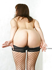 Busty brunette cougar in fishnets spreads her long legs exposing her shaved pussy