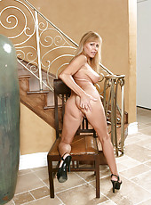 Lovely Nicole Moore sitting in chair and spreads her legs to display pink pussy
