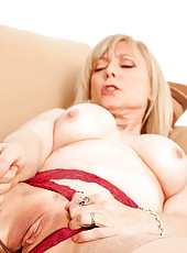 Enticing granny flaunts her big boobs while pleasuring herself with a toy