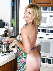 Naked housewife wearing an apron exposes her tits and sweet cougar snatch in the kitchen