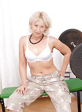 Seductive blonde milf strips her clothes off and spreads her pink snatch while sitting on a weight bench