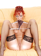 Redhead mature lady stuffs her succulant pussy with a glass dildo