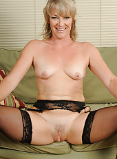 Hot blonde MILF Tina in stockings and ligerie spreads her long legs