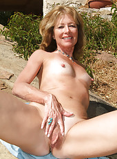 61 year old Janet L peels of her blue jeans and spreads on the rocks