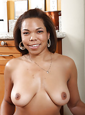 Ebony MILF Rena quickly peels her tight clothes in the kitchen