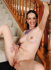 Sexy long haired brunette Beth M spreads her legs wide on the stairs