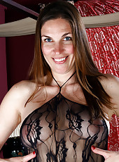 Sexy brunette MILF Phoebe in a black fishnet bodysuit shows ass