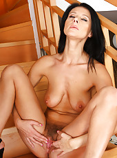 Mature brunette model Enza from AllOver30 spreads wide on the stairs