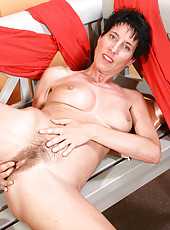 Thin mature brunette shows off her hairy pits and hot furry pussy