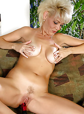 Blonde MILF slides a big red dildo into her mature pussy here