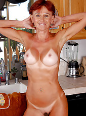 Redheaded MILF Kate spreads her tight asscheeks in the kitchen