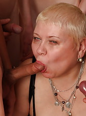Eager mom sucking on five hard young cocks at the same time