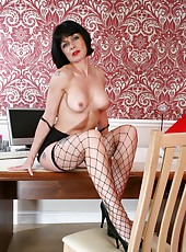 Mature milf Barbie Stroker spreads herself in fence net stockings