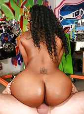 Amazing rumpolicious round booty babe gets her juicy black pussy fucked hard in these auto mechanic back office fucking pics and big video