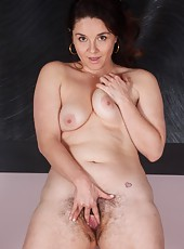 Maxine Holloway loves surprising her lovers. She comes home early from a charity event and does a striptease. She slowly strips off her red dress and shows them her pretty hairy pussy and hard nipples.