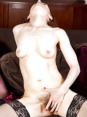 Hairy girl Amanda sits on her couch. She spreads her legs, tufts of pussy hair visible even though she