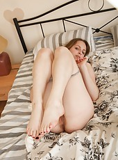 Katie pulls off her socks in the bedroom, and then her pretty pink panties. Her sexy hairy pussy is getting moist with excitement.