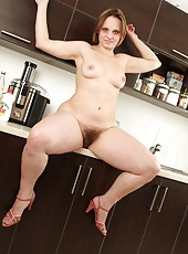 Mature Saxana slowly strips in the kitchen and rests her plump soft body on the bench top while she plays with her furry box.