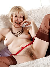 Experienced natural vixen Hazel sneaks her hand up her skirt and a finger into her mature hairy pussy on the couch.