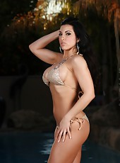 Sexy busty brunette, Brianna Jordan, looks stunning in her naughty gold bikini.  She puts on a sexy striptease revealing her big boobs, smooth pussy, and hot body.