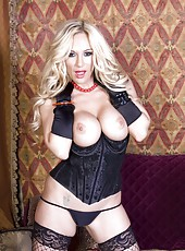 Busty blonde babe, Tyler Faith, looks hot in a black bustier, black fishnet stockings, and black gloves.