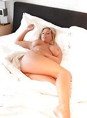 Amber Lynn Bach rolls around the bed totally naked and masturbates.