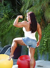 Bodybuilder Amber Deluca flexes her big strong body as she strips outdoors.
