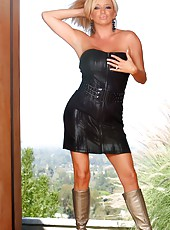Naughty busty blonde, Rachel Aziani, poses in her black leather dress and high heel boots.  She unzips her dress to reveal her incredible big boobs and hot body.