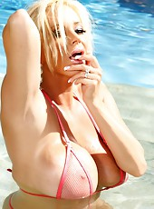 Busty blonde babe, Rachel Aziani, takes a dip in the pool wearing her mesh bikini and gives you a real good look at everything.