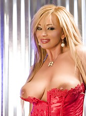 Busty Rachel Aziani loves posing with her favorite toy, the Sybian!  Blonde babe, Rachel, looks amazing in her red corset and getting ready for a wild ride!
