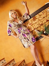 Sexy busty blonde, Mary Carey, poses on the stairs wearing her pretty dress.  Feeling a little frisky, Mary shows off pantyless pussy and big tits!