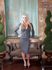 Hot blonde bombshell Mary Carey takes off her sexy business suit to expose her huge tits and bald pussy.