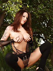 Busty brunette babe, Nikki Nova, poses in her black fishnet bodysuit and keeps warm with her thigh highs and hot thoughts.