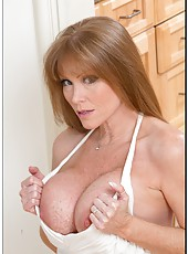 Charming lady Darla Crane posing at the kitchen and showing big boobs