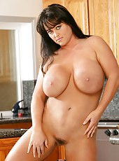 Fancy bombshell Indianna Jaymes posing in kitchen and tasting a wiener