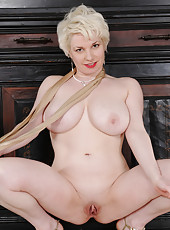 Blonde and busty Goldie Ray slips off her gold elegant dress in here