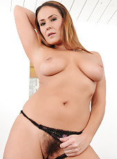 Busty all natural MILF Elexis Monroe posing naked on the leather sofa