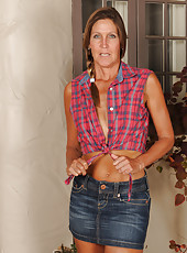 Thin 50 year old LA Valkenberg slips out of her short denim miniskirt