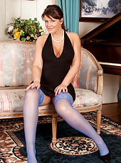 Elegant milf struts her stuff in a sexy black dress and blue stockings