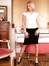 Blonde Anilos Scarlet slips off her office attire revealing her pink bra and panties