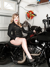 Hot pinup mom in leather shows off her curves on a motorcycle