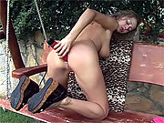 Busty babe is masturbating on an old bench