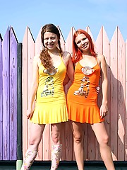 Two horny and cute lesbians playing in front of a fence