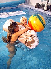 Two teenage girls having fun with their own blowup doll