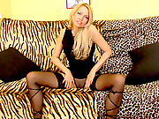 Seductive long blonde haired cougar spreads her legs on the couch