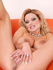 Beautiful big breasted Anilos cougar gently fucks her moist pussy with a big dildo on the sofa