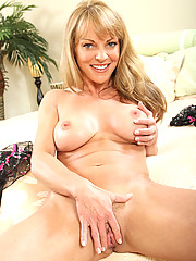 Lovely cougar Shayla Laveaux caresses her pussy while massaging her big boobs in bed