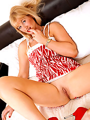 Nude Anilos cougar Suzy fucks her seasoned pussy with her favorite glass dildo in her bed